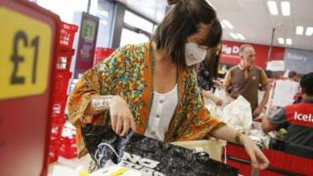 A customer wears a face mask while shopping at Iceland in Islington