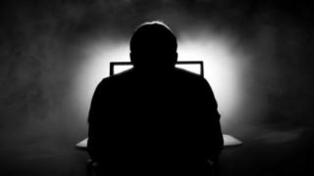 silhouette of man sat in front of computer
