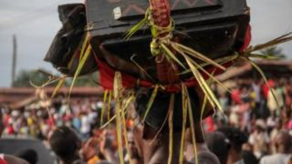 """A man carrying a """"magic"""" wooden box on his head through the streets of Arondizuogu during the Ikeji Festival in Nigeria"""