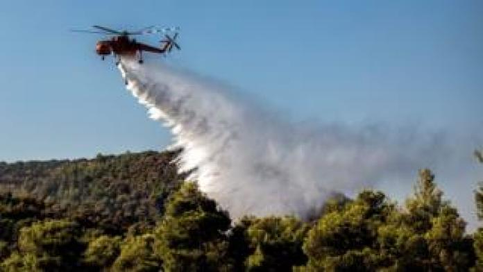 Un hélicoptère de lutte contre les incendies larguant de l'eau sur une forêt pour calmer les flammes