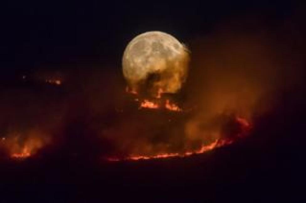 The full moon rises behind burning moorland