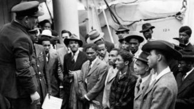 Jamaican men being welcomed by RAF officials after the Empire Windrush arrrived at Tilbury on 22 June 1948