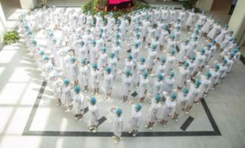 A crowd of nurses stand in the shape of a heart as they recite an oath