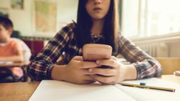 تلميذة تستخدم هاتفا نقالا