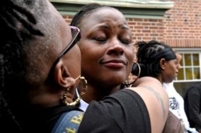 Blondina Bean is comforted while she cries at a memorial for her son, George Phillips, who was a victim of gun homicide at the age of 19