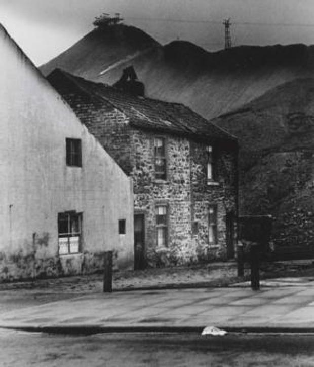 A photograph of cottages with a the hills of a coal mine in the background