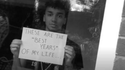 """A young person holds up a sign that reads """"these are the best years of my life"""""""