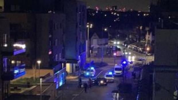 A picture of police cars with blue flashing lights at the scene