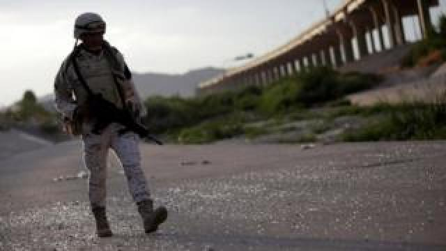 A member of the Mexican National Guard patrols on the banks of the Rio Bravo river at the border between Mexico and the US as seen from Ciudad Juarez