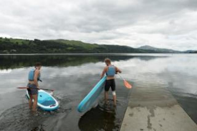 Men wearing life vests get ready with their paddle boards as the Bala Adventure and Watersports Centre in Bala, Gwynedd