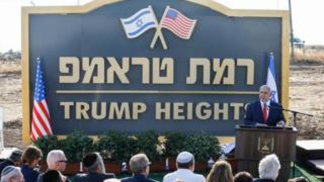 """Israeli Prime Minister Benjamin Netanyahu gives a speech before the newly-unveiled sign for the new settlement of """"Ramat Trump"""", or """"Trump Heights"""""""