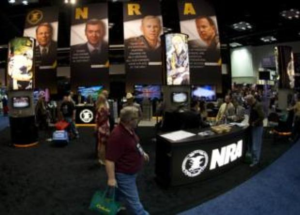onvention goers walk through the NRA booth at the143rd NRA Annual Meetings and Exhibits at the Indiana Convention Center in Indianapolis, Indiana on April 25, 2014