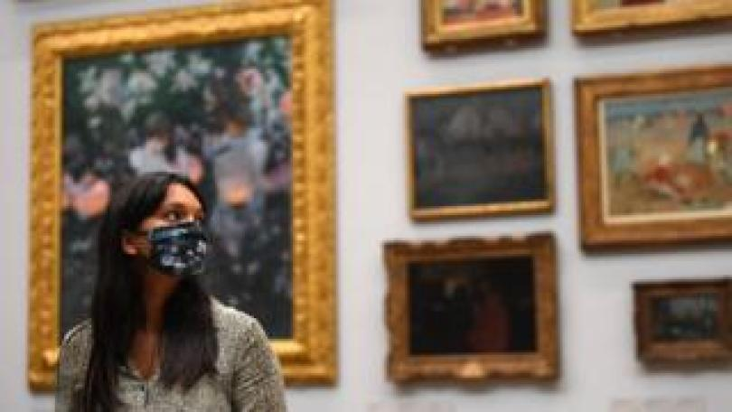 Gallery worker in face covering poses at Tate Britain ahead of its reopening