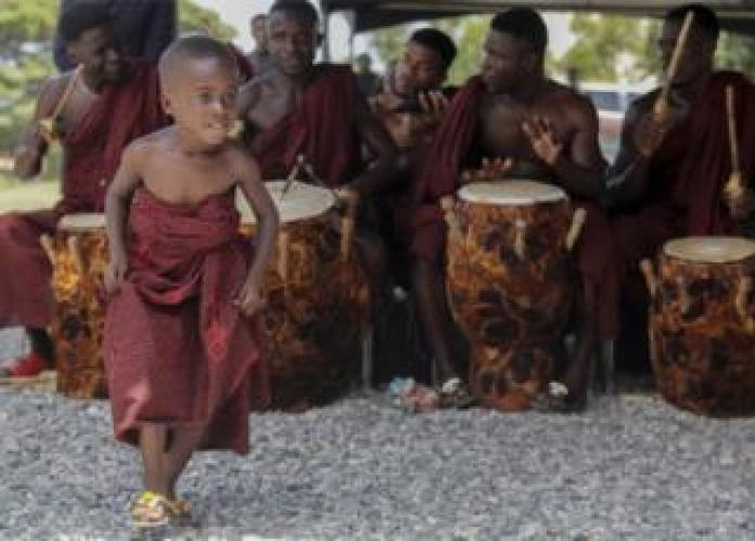 A boy dances as a drummer in traditional clothing at the Accra International Conference Center, where the body of the late Kofi Annan was placed in Accra, Ghana, on September 11, 2018 in the state