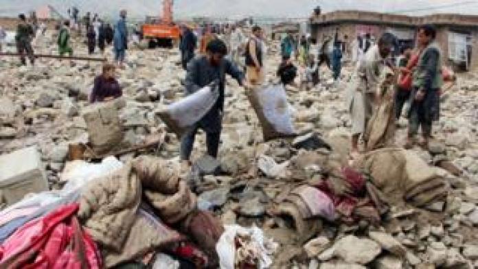 Food Afghan men search for their belongings after floods in Charikar