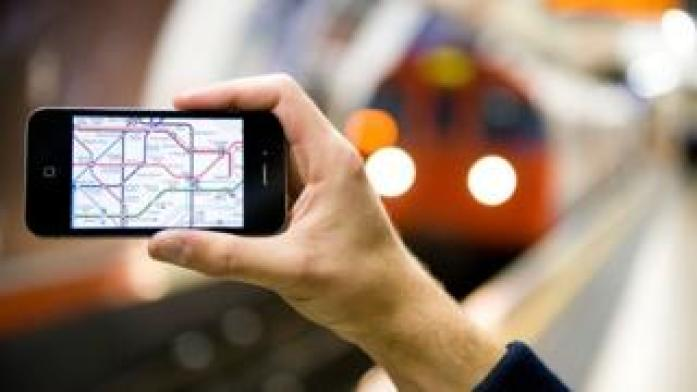Man holds phone on London Underground