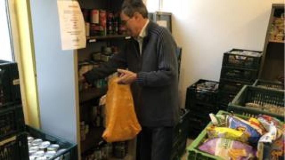 A volunteer fills a bag of food