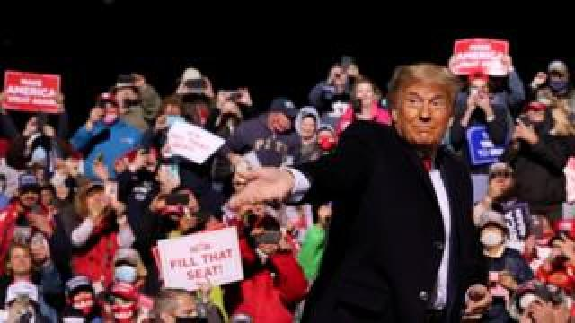 US President Donald Trump throws face masks to the crowd in Pennsylvania