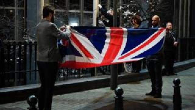 The UK flag is taken down and folded up outside the European Parliament building in Brussels.
