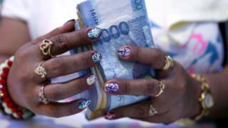 A casino financier wearing rings and with painted fingernails