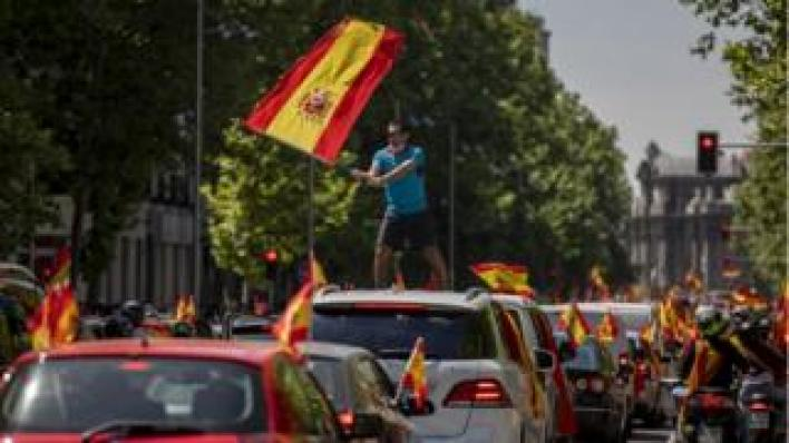 Image shows a man waves a Spanish flag as he takes part in an in-vehicle protest