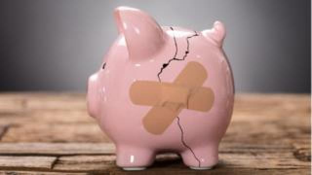 A cracked piggy bank with a plaster across it