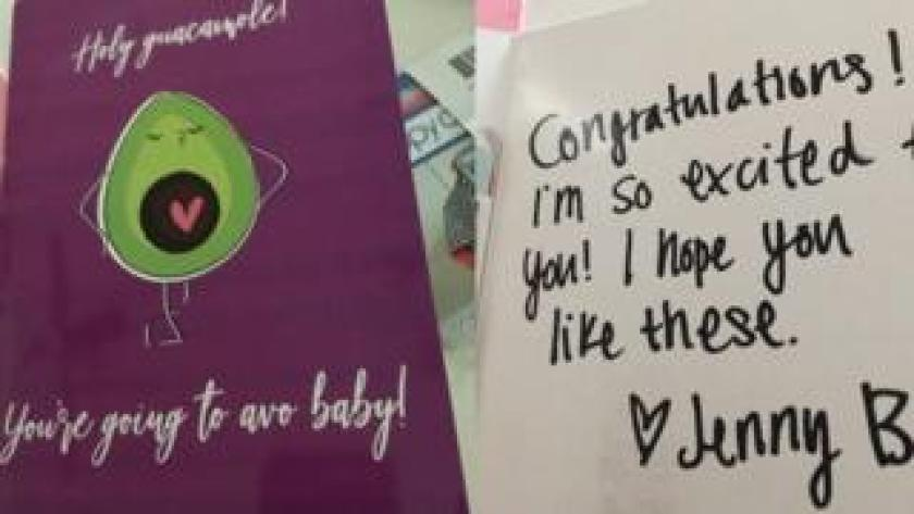 A card saying 'Holy guacamole, you're going to avo baby' next to a note saying 'Congratulations! I'm so excited for you! I hope you like these' signed by Jenny B