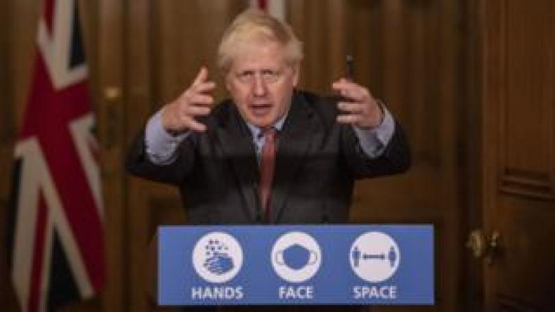Boris Johnson speaks at the podium for a No 10 press office - it reads 'Hands. Face. Space'. He is gesturing with his arms up