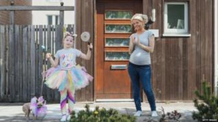Mother and daughter clapping outside their house