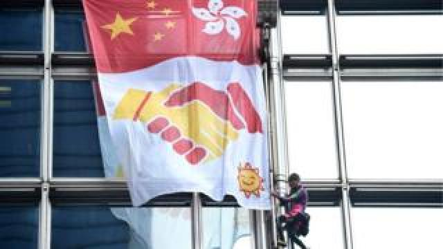 Climber and banner on skyscraper
