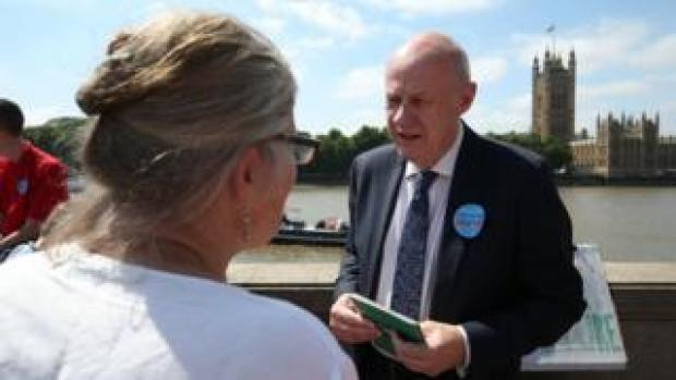 Tory MP Damian Green talks to one of his constituents on the protest