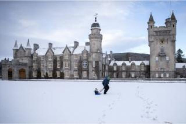 Geraint Stone pulls his two-year-old son Arthur on his sledge across the snow-covered lawn in front of Balmoral Castle, Royal Deeside