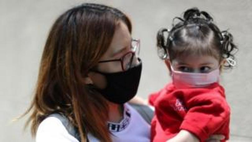 A woman holds her daughter near a hospital in Los Angeles, California. Photo: July 2020