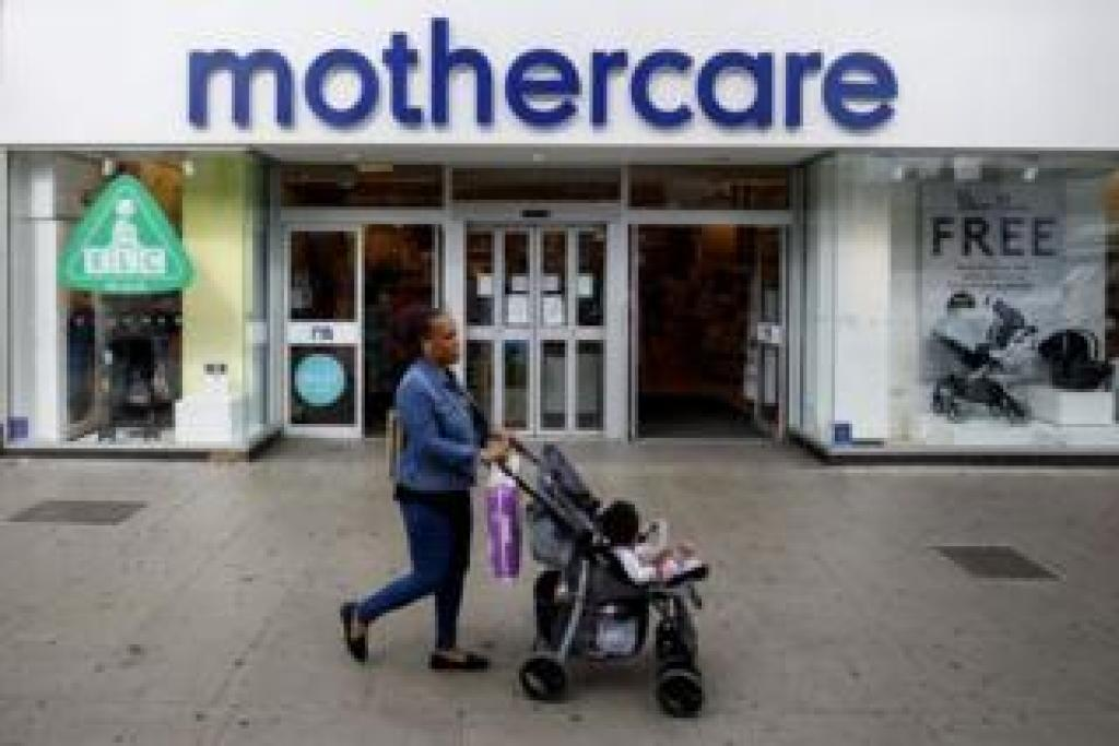 Woman with push chair walks past mothercare store