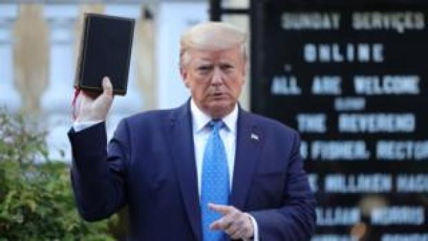 Donald Trump holding a Bible in front of a church