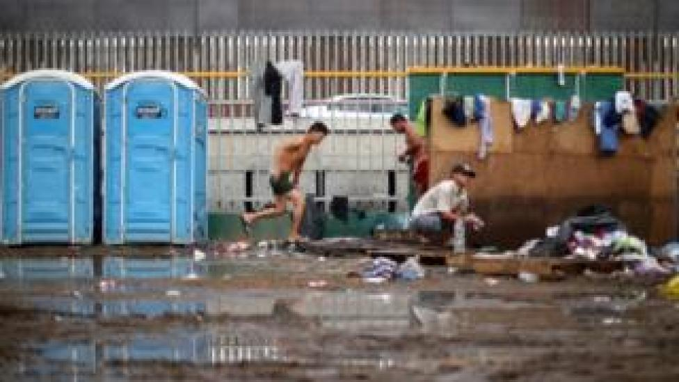 Migrants shower in front of the border wall with the United States in Tijuana on 28 November, 2018