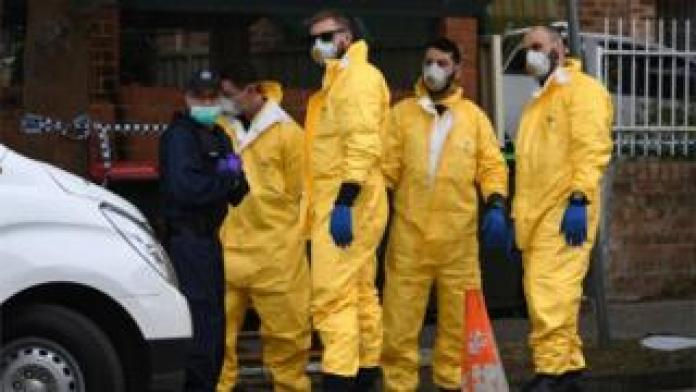 Workers in protective clothing outside a Sydney address