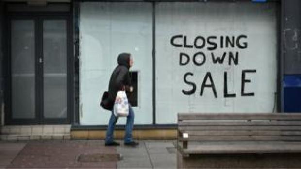 A pedestrian walks past a boarded-up shop in Sunderland