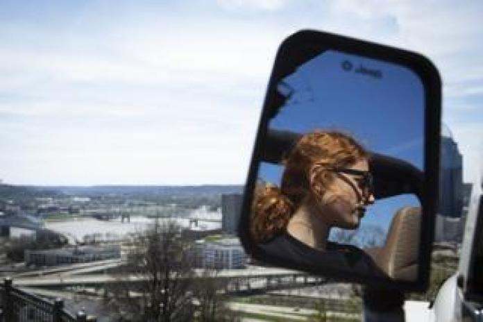 The reflection of Maddie Sabina's sister in the rear view mirror