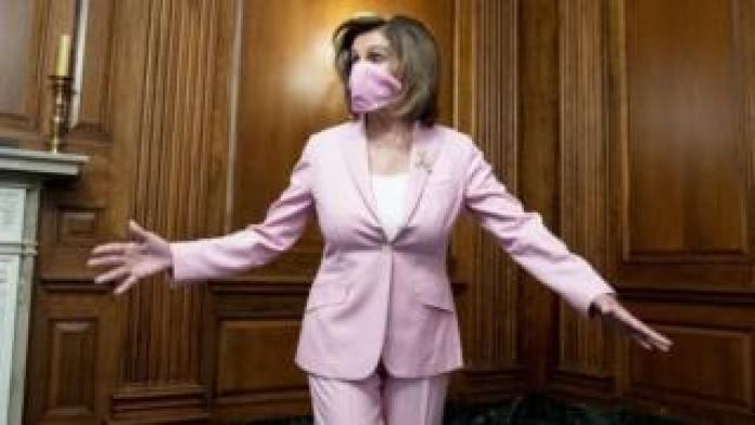 Nancy Pelosi wears a mask that matches her pink suit