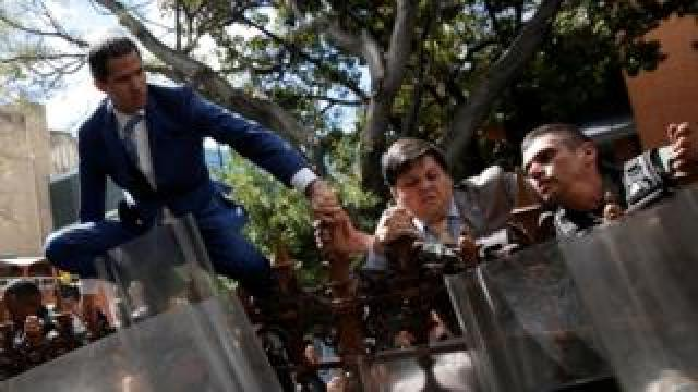 Juan Guaidó climbing a fence in front of the National Assembly