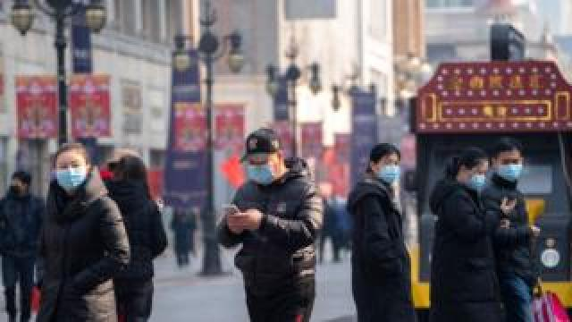 People wearing masks walking on the famous business street of Binjiang Dao, at downtown Tianjin.
