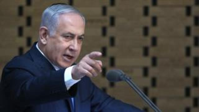 Mr Netanyahu points into the crowd from a podium in this 10 October image