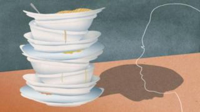 The profile of a woman next to a pile of plates