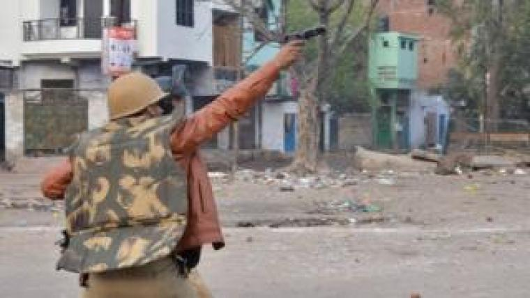 PressMirchi A police officer aims his gun towards protesters during demonstrations against India's new citizenship law in in Kanpur
