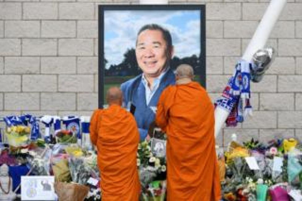 Buddhist monks lay tributes by a photograph of Leicester City Football Club's chairman Vichai Srivaddhanaprabha