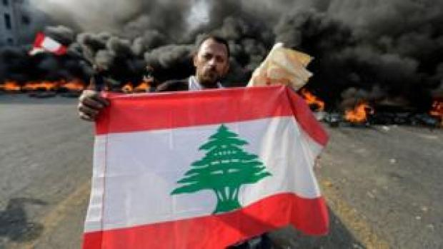 Protester holds a Lebanese flag as tires burn behind
