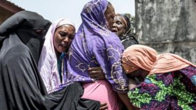 Women hug each other in grief in Conakry, Guinea - Sunday 1 March 2020