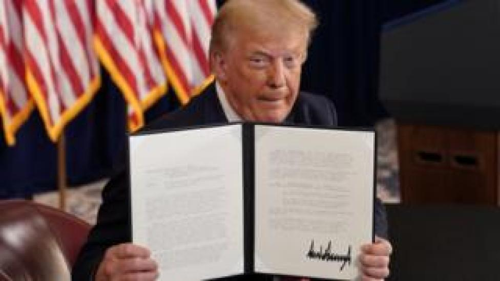 trump US President Donald Trump shows signed executive orders for economic relief