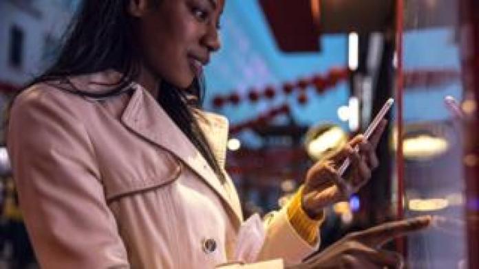 Frau auf Smartphone und interaktiven Touchscreen
